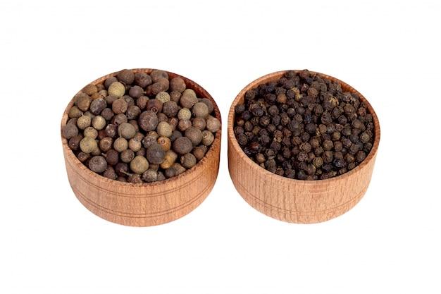 Piment in een houten kom. zwarte peper. geïsoleerd op witte achtergrond.