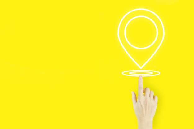 Pin adres locatie concept. de handvinger van de jonge vrouw wijst met hologram locatiemarkering op gele achtergrond. concept van internetkaarten en navigatie.