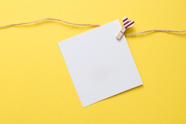 Pin met hart en witte kaart op gele achtergrond voor valentijnsdag