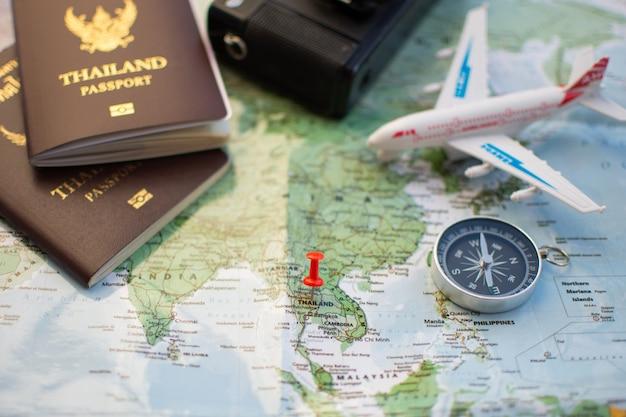 Pin op locatiekaart voor reisplan met paspoort kompas camera en notebook.