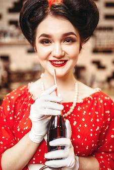 Pin-up girl met make-up drinken populaire koolzuurhoudende drank, 50 amerikaanse mode. rode jurk met stippen, vintage stijl