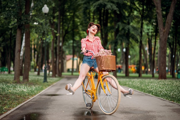 Pin-up girl op retro fiets, vintage amerikaanse mode. leuke vrouw in pinup-stijl