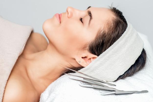 Pincet in de buurt van mooie vrouw met gesloten ogen liggen klaar voor huidverzorging en procedures.
