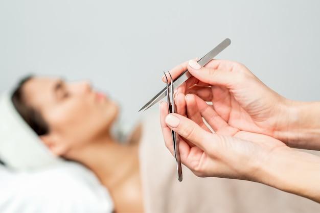 Pincet in handen van schoonheidsspecialiste op vrouw vóór procedure voor wimperextensies.