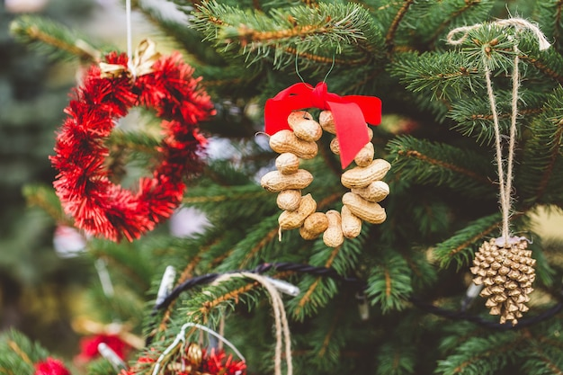 Pinda's en goud geschilderde gouden dennenappel handgemaakte decoratie op kerstboom.