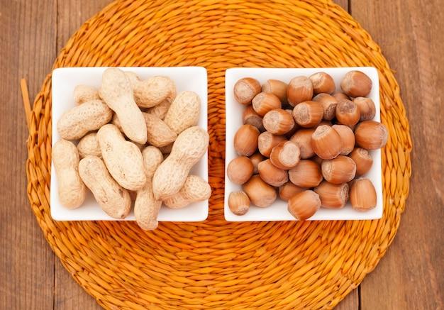 Pinda's en hazelnoten in een witte kom op een rieten servet
