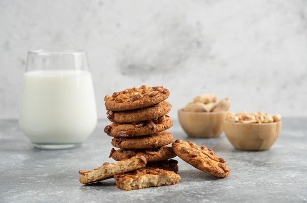 Pinda's, glas melk en koekjes met biologische pinda's op marmeren tafel.