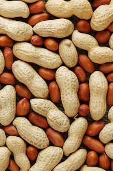 Pinda's in een schaal gemengd met gepeld, de textuur van het voedsel van bonen