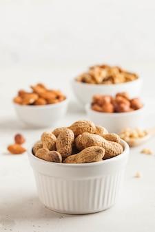 Pinda's in hun schelpen. geassorteerde noten, amandelen, hazelnoten, walnoten. gezonde snacks. kopieer ruimte.