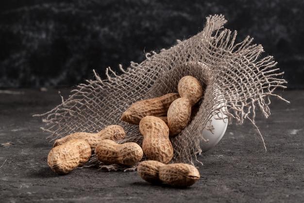 Pinda's op een donkere achtergrond. gebakken pinda's. noten.