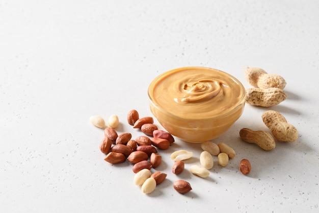 Pindadeeg en noten op witte achtergrond voor gezond voedingsconcept.