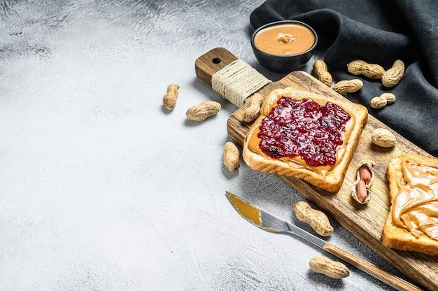 Pindakaas en gelei op witte broodtoosts