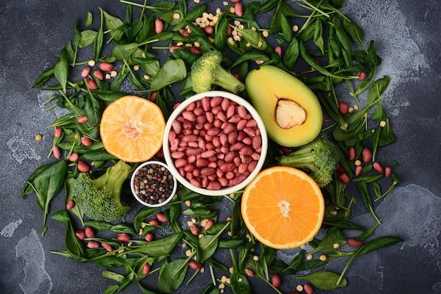 Pindakaas in een kom, gesneden avocado en sinaasappelhelften liggen op spinazieblaadjes