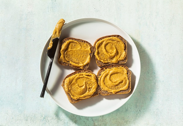 Pindakaas op brood en een mes op een bord op tafel