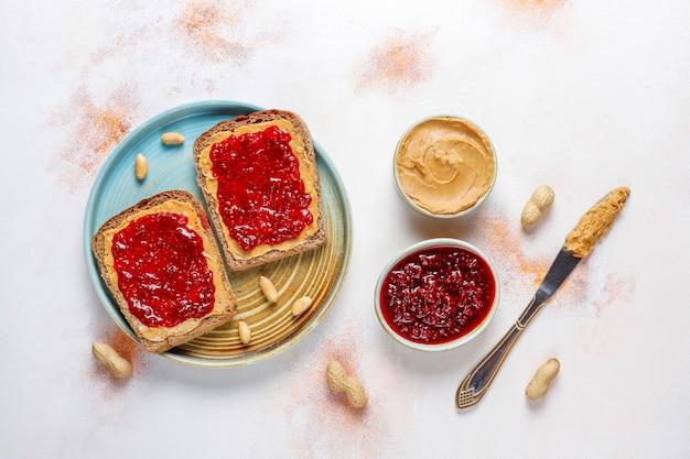 Pindakaasbroodjes of toast met frambozenjam.