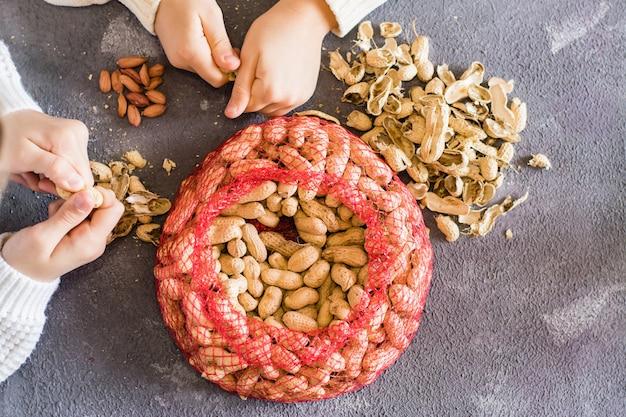 Pindaschillen en een netje met bruine noten op tafel. babyhanden die noten op de achtergrond pellen. levensstijl. bovenaanzicht