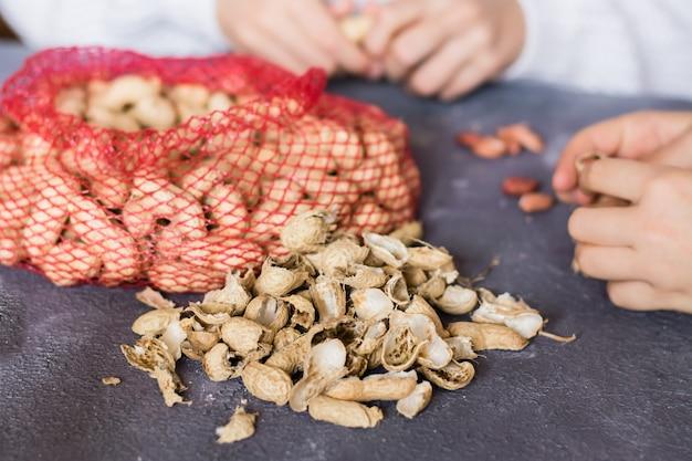 Pindaschillen en een netje met bruine noten op tafel. babyhanden die noten op de achtergrond pellen. levensstijl