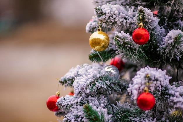 Pine besneeuwde tak met rode en gouden kerstballen.