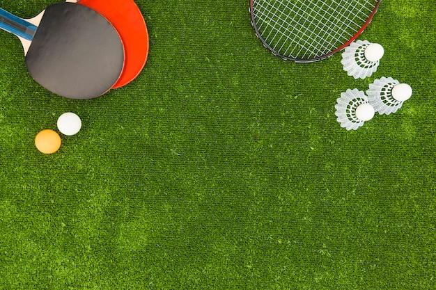 Pingpongballen; shuttle; badminton en rackets op groene grasmatten