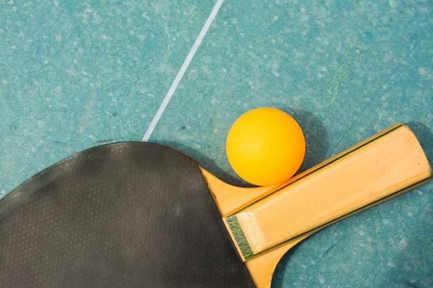Pingpongpeddels en bal op retro blauw