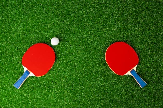 Pingpongrackets en bal op gras