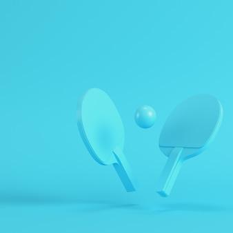 Pingpongrackets met bal op heldere blauwe achtergrond in pastelkleuren. minimalisme concept