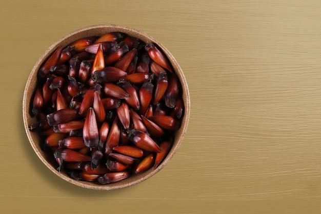 Pinion, traditioneel braziliaans eten, araucaria-zaad. bovenaanzicht op kleurrijke houten achtergrond.