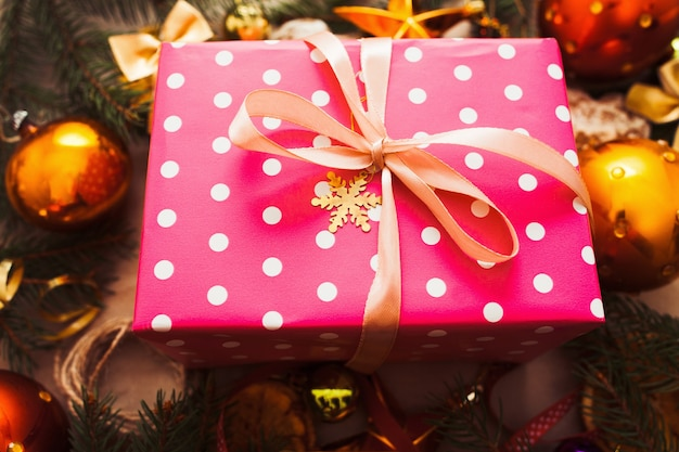 Pink christmas gift met gouden ballen close-up