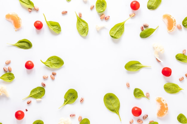 Pinto bean; groenten en stukjes sinaasappel gerangschikt op witte achtergrond