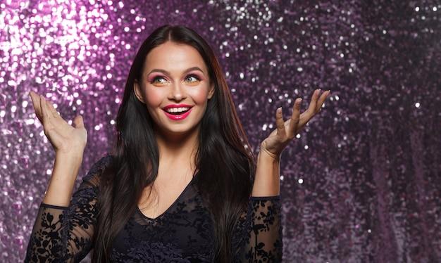Pinup meisje glimlacht in een avondjurk op de achtergrond van de sparkles bright make-up plezier en feest