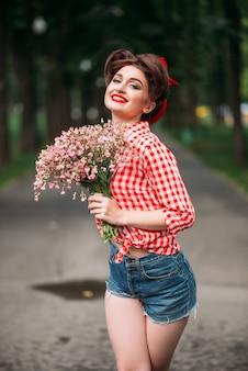 Pinup meisje met boeket bloemen, retro mode