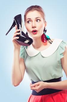Pinup-stijl meisje beantwoordt een schoenentelefoon