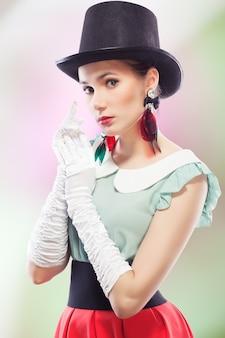 Pinup-stijl meisje met hoge hoed en handschoenen