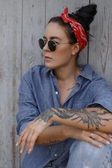Pinup-stijl. stijlvolle vrouw met een bandana en zonnebril in mode jeans kleding zit in de buurt van een houten muur. tatoeage op de hand
