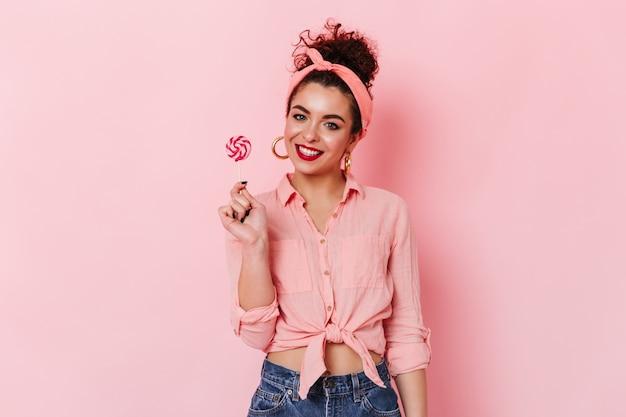 Pinup vrouw in stijlvolle hoofdband en roze shirt poseren op geïsoleerde ruimte en lolly te houden.