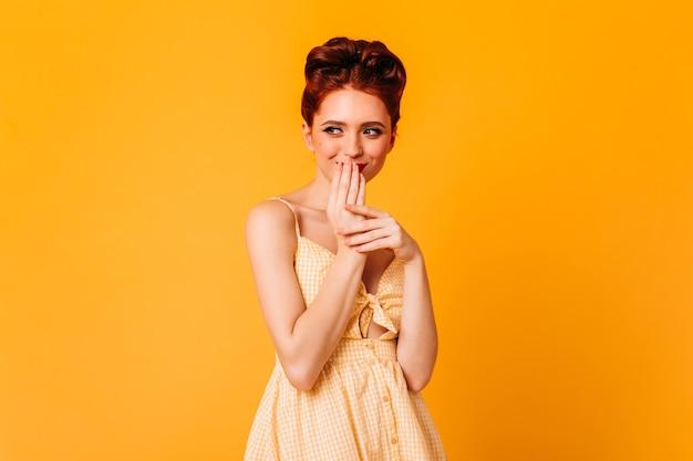 Pinupmeisje die en mond met handen glimlachen behandelen. studio shot van blithesome gembervrouw met elegant kapsel.