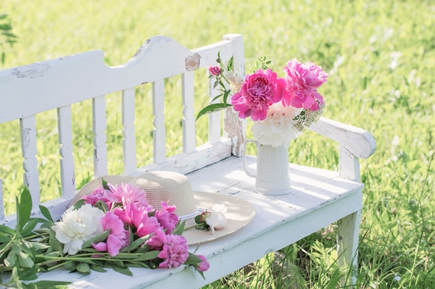 Pioen in kruik op witte houten bank in zomertuin