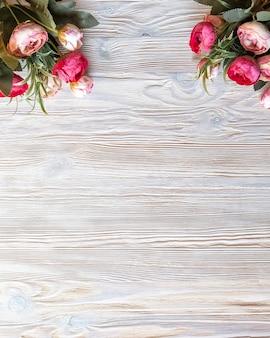 Pioenrozen bloemen achtergrond op een houten bord met frame. bovenaanzicht