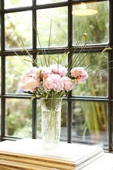 Pioenrozen bloemstuk in glazen vaas op tafel