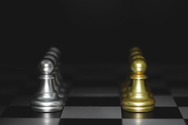 Pion schaakstukken slag, gouden en zilveren schaak op een schaakbord. concept voor strategie, zakelijke overwinning.