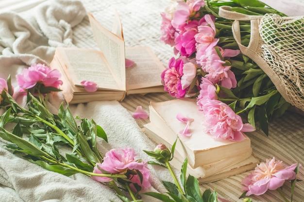 Pions bloemen en lentedecor op de boeken
