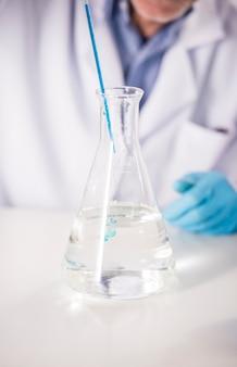 Pipetteer met druppel chemisch product boven fles wetenschappelijke beker.