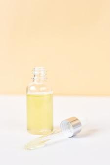 Pipetteer met etherische olie over fles op witte en gele achtergrond. natuurgeneeskunde concept. aromatherapie