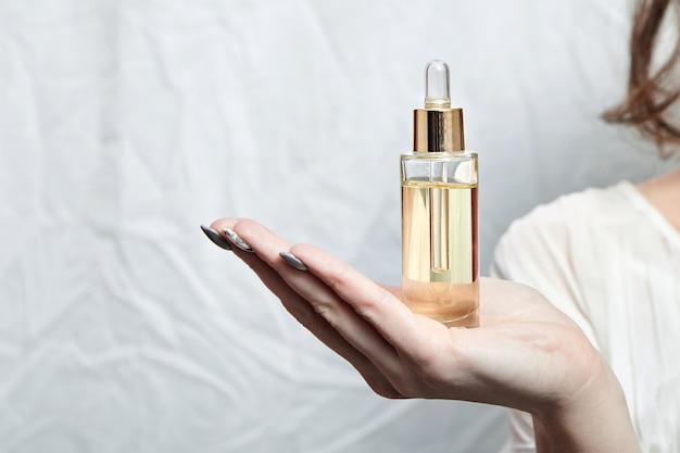 Pipetteerfles met cosmetische olie in vrouwelijke hand