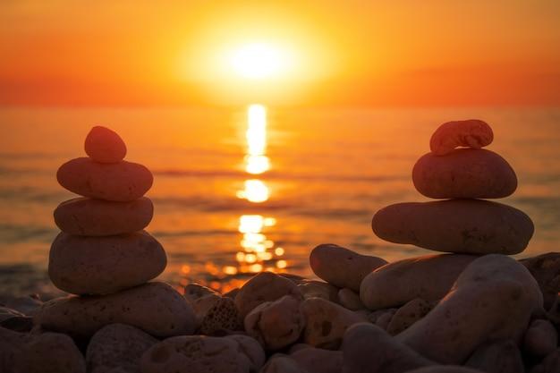 Piramide van de kleine steentjes op het strand. stenen, tegen de achtergrond van de kust tijdens zonsondergang