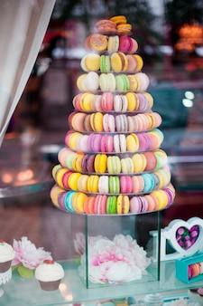 Piramide van diverse kleurrijke macarons in een etalage.