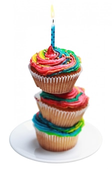 Piramide van drie kleurrijke cupcakes met een brandende kaars