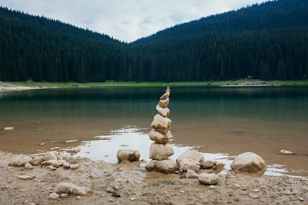 Piramide van stenen is samengesteld aan de oevers van een zwart meer in montenegro