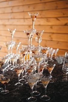 Piramide van wijnglazen met champagne. champagne wordt in de glazen gegoten. feestelijke aankleding van het evenement met een piramide van champagneglazen. splash en druppels.