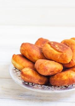 Piroshki - russisch gebakken bladerdeeg met koolvulling. traditionele russische kool gevuld gebakken gebak. magere taarten met kool. mooie zelfgemaakte taarten met kool in metalen schotels op wit